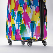 "American Tourister Moonlight 24"" Spinner in the color Popsicle."